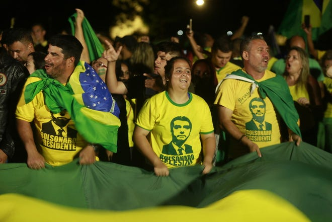 Supporters of Brazilian far-right presidential candidate Jair Bolsonaro celebrate his victory at the Ministries Esplanade on Sunday.