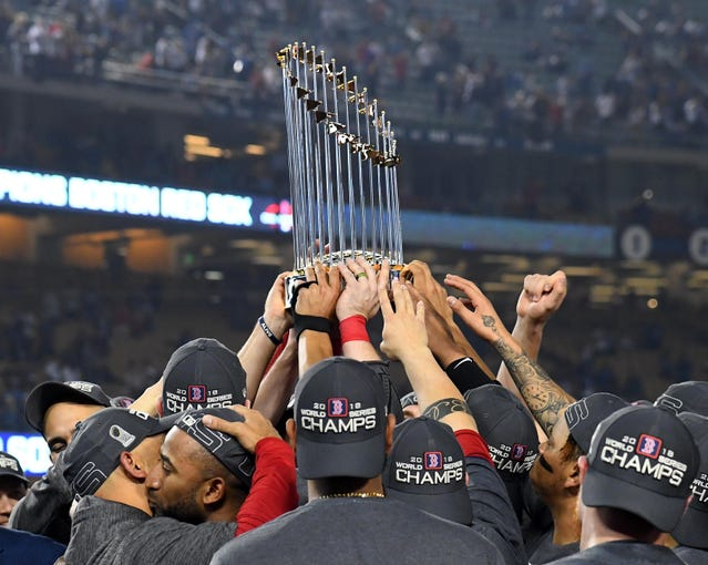 Red Sox players hoist the World Series trophy after the Game 5 win.