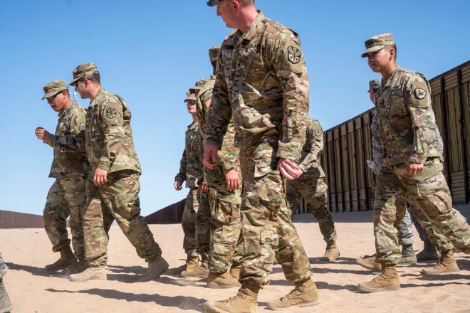 National Guard troops in San Luis, Ariz., walk near the U.S.-Mexico border on April 18, 2018.