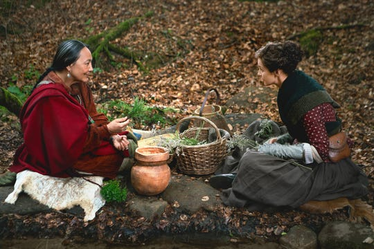 Adawehi (Tantoo Cardinal), left, and Claire (Caitriona Balfe) bond while gathering leaves by the lake in a scene from Starz's 'Outlander.'