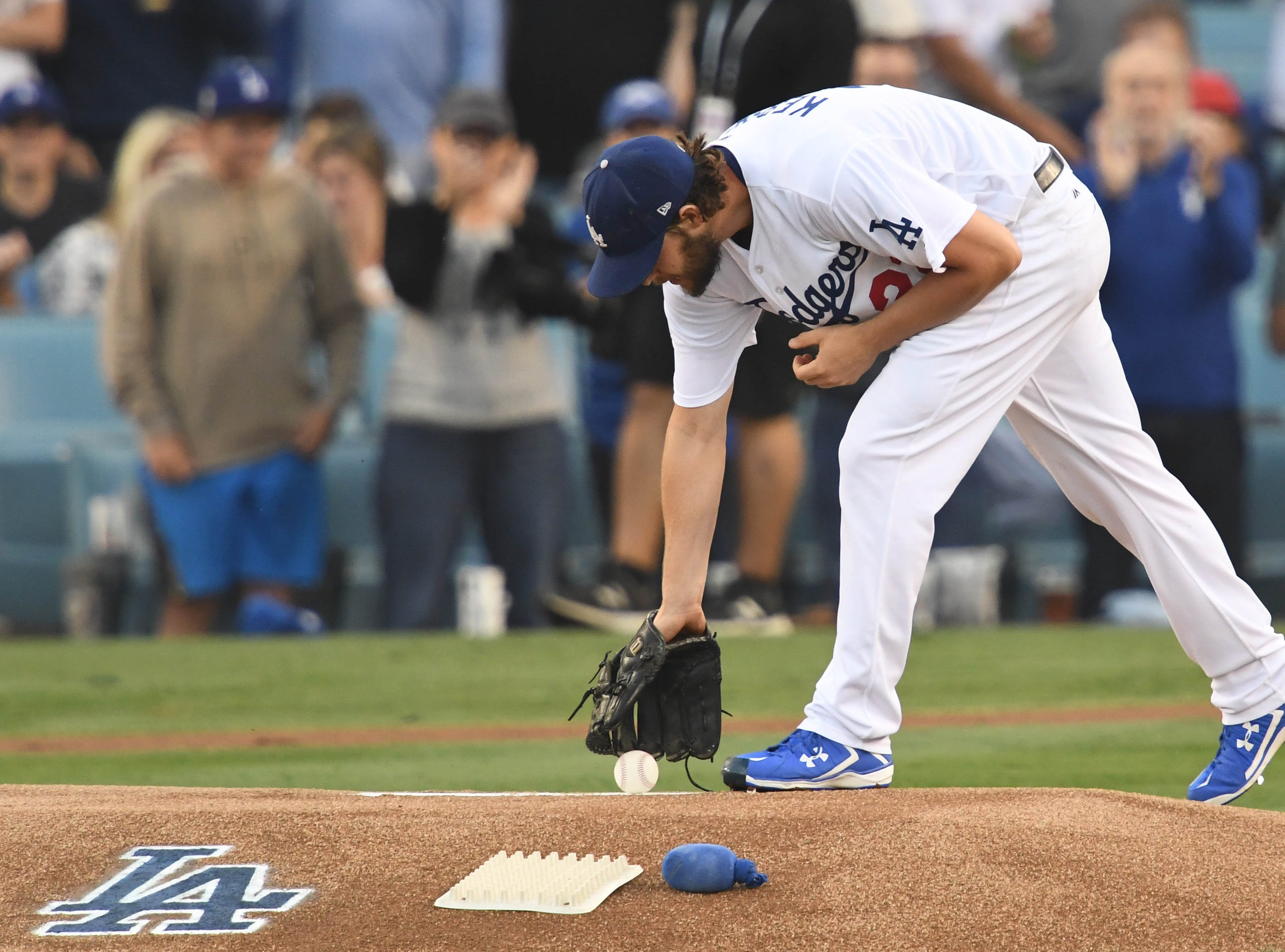 Game 5 at Dodger Stadium: Clayton Kershaw picks the ball up off the mound in the first inning.