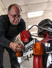 Keith Froias, worker at Hot Shot Cycles on South Murray Avenue in Anderson, places a moped card on the back of one at the store which has been selling them since 1970. Owner Paul Abercrombie says new laws for riders should be helpful.
