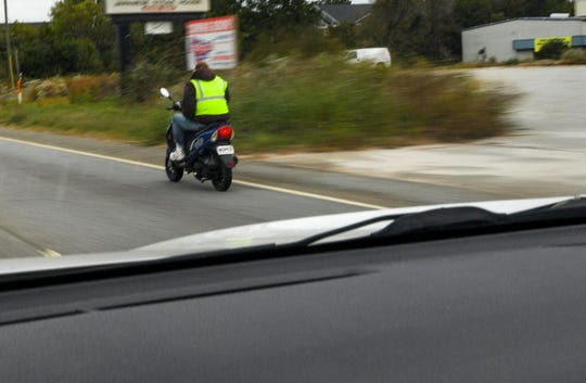 A moped rider stays close to the edge of State Highway 28 Bypass in Anderson, wearing a reflective vest and a moped tag marker in October.