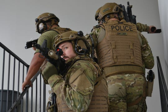 Alexandria Police SWAT team members move upstairs as they clear the terminal. Alexandria and Pineville SWAT teams as well as the Rapides Parish Sheriff's office joined the Louisiana National Guard for the training exercise in which terrorists took hostages at Esler Field.