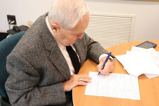 Toms River Mayor Thomas F. Kelaher signs closing documents as the township takes possession of the troubled Red Carpet Inn Tuesday.
