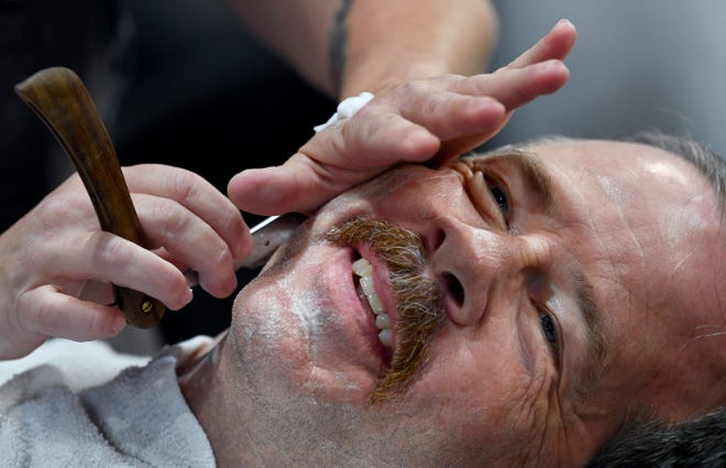 Nichole Kitchen shaves former Abilene Fire Chief Larry Bell at The King's Barber Tuesday. The barber shop is located inside Lone Star Dry Goods, where several men were getting shaved there for the last time before the United Way's No Shave November.