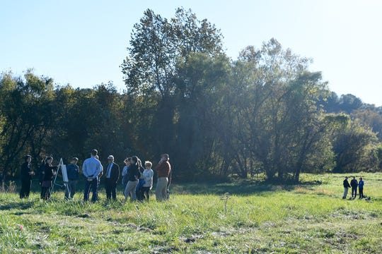 Groups tour the 5-acre lot where a junkyard once stood to view RiverLink's draft master plan of Karen Cragnolin Park on Amboy Road Oct. 29, 2018.