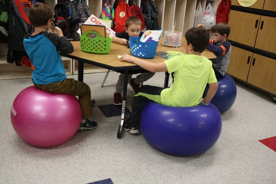 Clockwise from left, Jack Vaseleck, Jayden Paoier, Riley Hayes and Noah Maloney, all 7 years old, sit at the yoga ball table in Jessica McBreen's second-grade classroom on Oct. 26.
