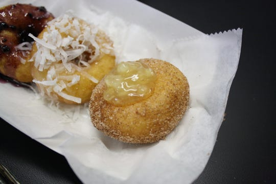 From left: Blue Velvet (blueberry glaze), Caramel Delight (caramel glaze with coconut) and American Pie (apple pie center filled with cinnamon and sugar) are served up at the JukeBox Donut Shop.