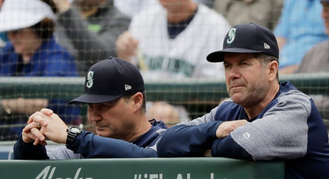 Hitting coach Edgar Martinez, right, stands with manager Scott Servais during a May game in Seattle against the Texas Rangers. The team announced Tuesday that Martinez is stepping down as hitting coach to become an organizational batting adviser.