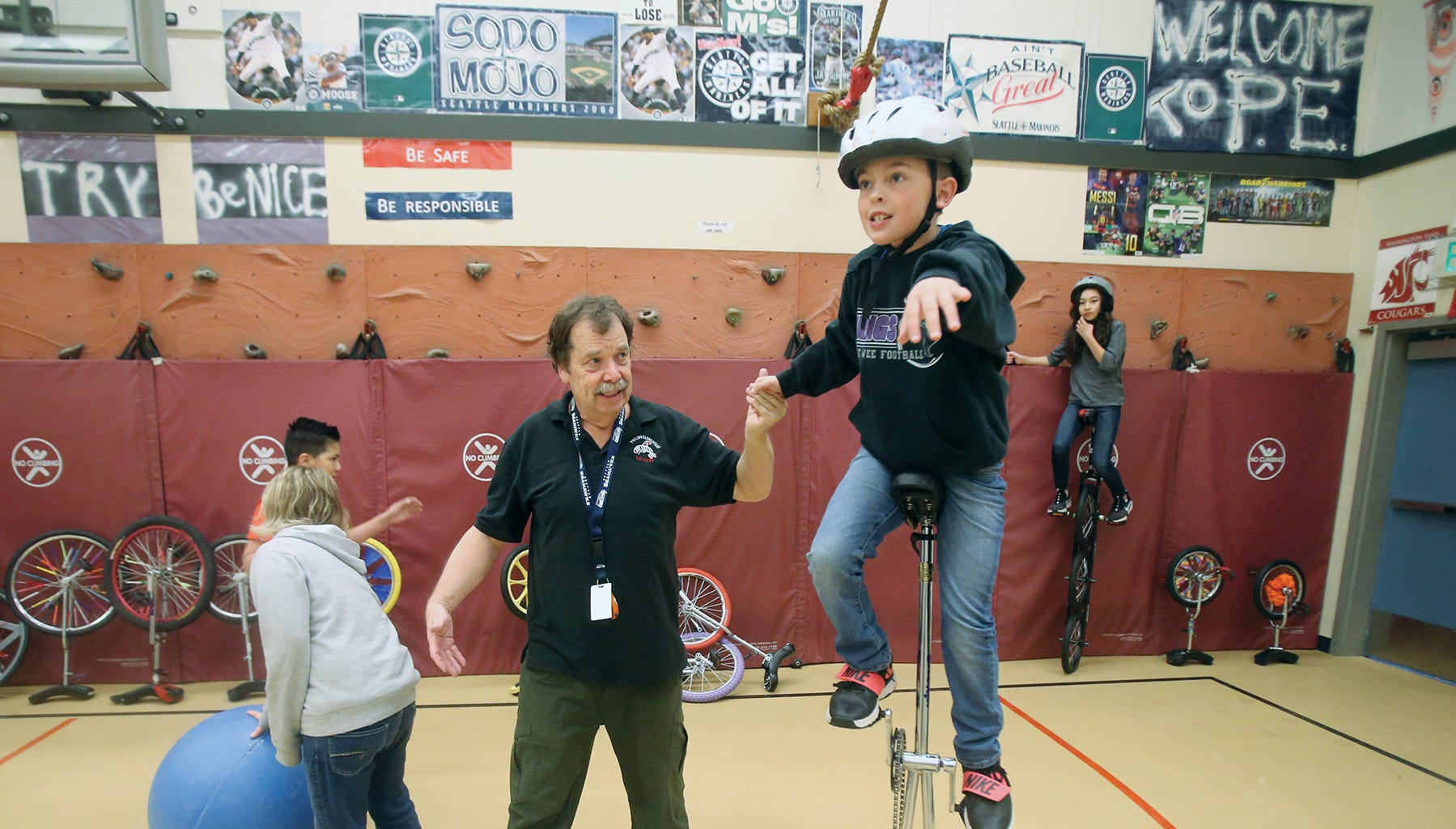 Robert Webb PE specialist at Poulsbo Elementary School helps fifth grade student Nathan Duerr, 11, with his unicycle balance in class.
