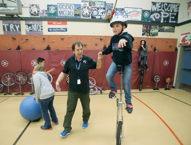 Robert Webb, a P.E. teacher at Poulsbo Elementary, helps fifth-grader Nathan Duerr, 11, with his unicycle balance in class.