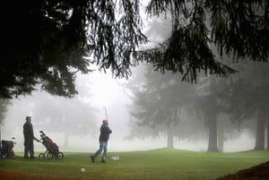 A golfer swings in the fog at Village Greens Golf Course in Port Orchard.