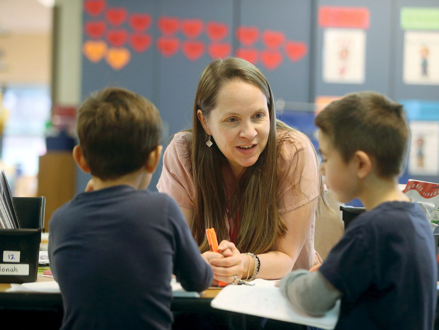 Kjersti Johnson, a kindergarten teacher at Poulsbo Elementary helps students sound out the word apple in class.