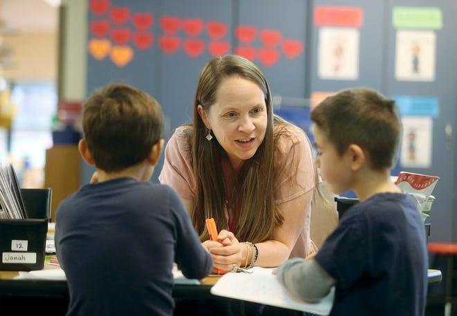 Kjersti Johnson, a kindergarten teacher at Poulsbo Elementary, helps students sound out the word apple in class.