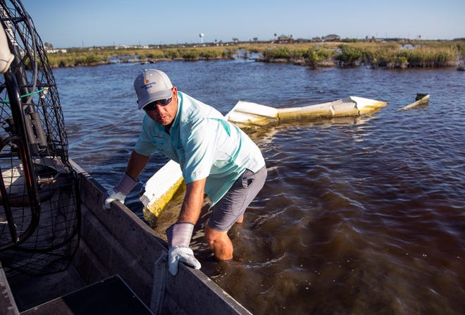 Brett Phillips pulls roofing material from Cove Harbor in Aransas County on Tuesday, October 30, 2018 during a cleanup organized by Keep Aransas County Beautiful.Volunteers were working to clean debris from the wetlands and harbor that was scattered by Hurricane Harvey over 14 months ago.