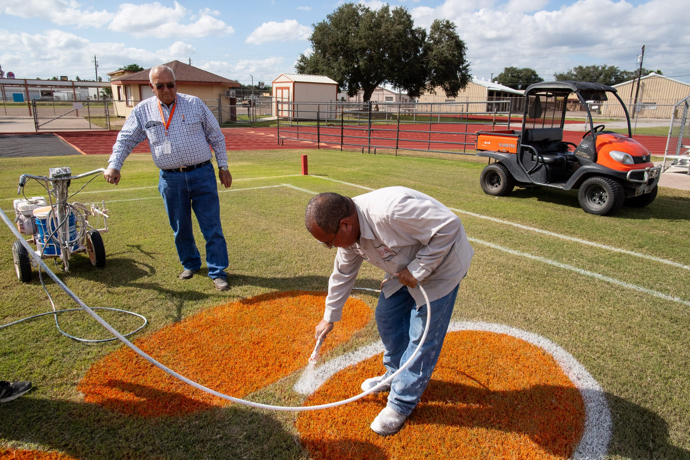 Billy Riojas grounds keeper at Alice High School's Coyote Stadium supervisors as the end zone is painted on Tuesday, Oct. 30, 2-018