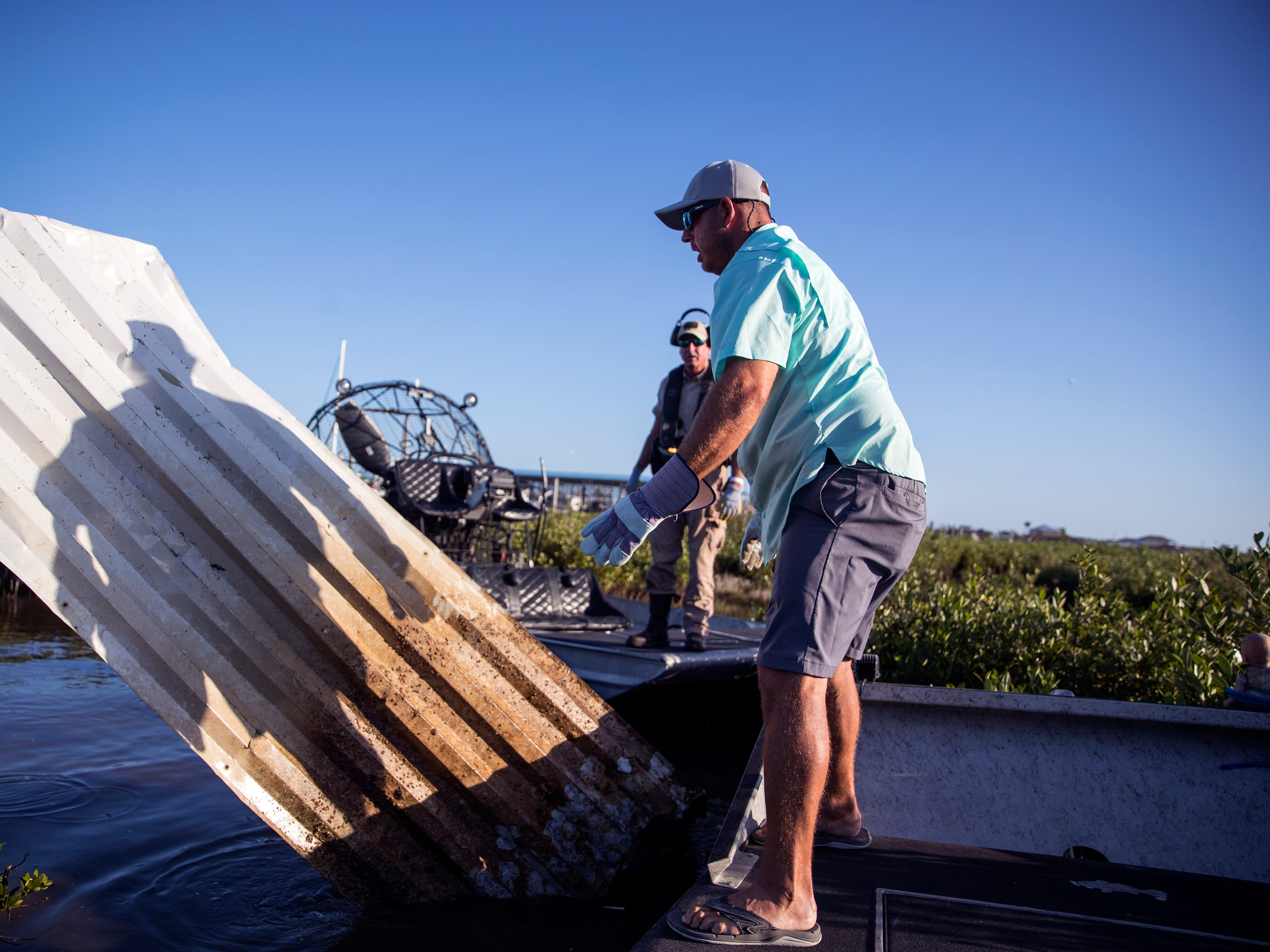 Texas Game Warden Scott McLeod (left) and Brett Phillips pull roofing material from Cove Harbor in Aransas County on Tuesday, October 30, 2018 during a cleanup organized by Keep Aransas County Beautiful.Volunteers were working to clean debris from the wetlands and harbor that was scattered by Hurricane Harvey over 14 months ago.