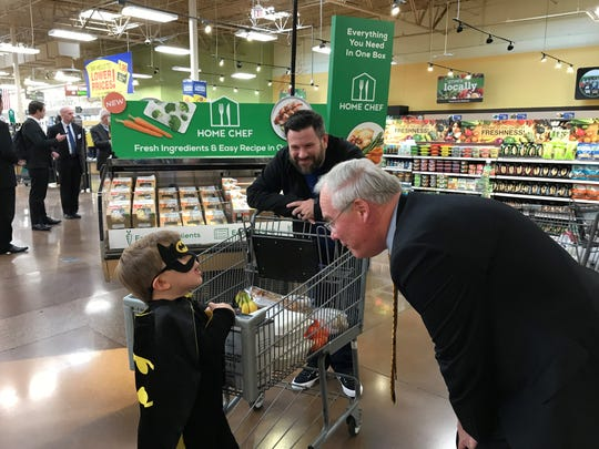 Kroger CEO Rodney McMullen (right) greets Batman (3-year-old Shepherd) and Patrick Taylor of Covington to the Newport Kroger Marketplace.