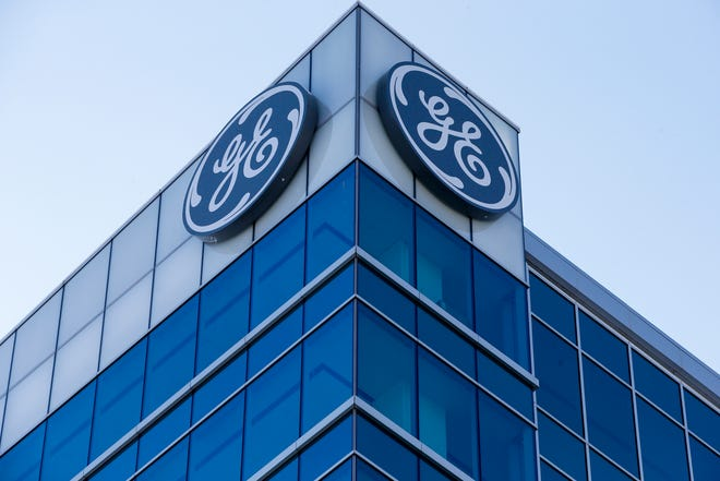 The General Electric logo is displayed at the top of their Global Operations Center, in the Banks development of downtown Cincinnati. General Electric Co. reports earnings Tuesday, Oct. 30. (AP Photo/John Minchillo, File)