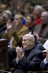 Archbishop Daniel Pilarczyk applauds in appreciation at the Cincinnati Symphony Orchestra's 2002 concert performed in his honor at St. Peter in Chains Cathedral. Pilarczyk was a longtime CSO patron.