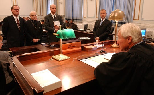 Archbishop Daniel Pilarczyk stands with his attorneys Tom Miller (left) and Mark VanderLaan (center) in 2003 before Judge Richard A. Niehaus as they plead no contest to five counts of failure to report a felony in cases related to sexual molestation by priests in the archdiocese. Hamilton County Prosecutor Mike Allen (right) brought the charges.