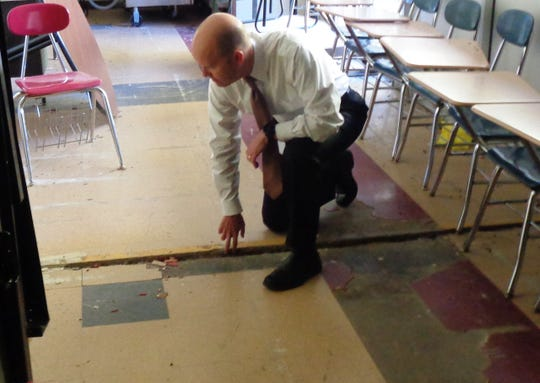 Indian Hill Schools Superintendent Dr. Mark Miles kneels to point out a break in the floor in an unusable closed off section of the current Indian Hill Middle School building.