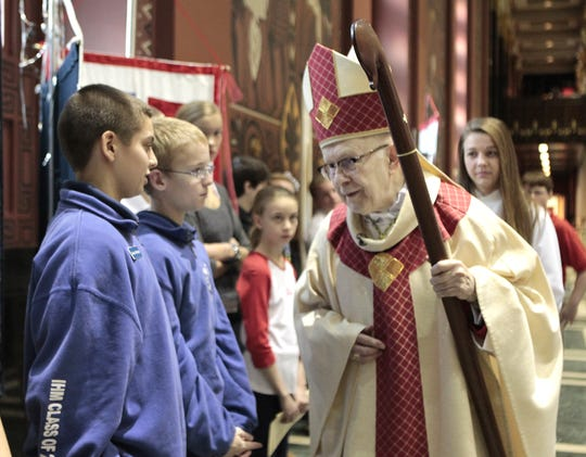 Archbishop Daniel E. Pilarczyk greets Immaculate Heart of Mary eighth-graders Joshua McSwigan, left, and Matthew Cornell during Catholic Schools Week Mass at St. Peter in Chains Church downtown in 2012.