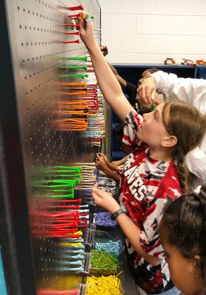 Students work with the pegboard wall in the new Science, Technology, Engineering, Arts and Math (STEAM) iLab in the Indian Hill Elementary School funded by the Koch Foundation.