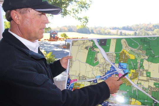 Keith Boyd indicates on a map where the new development is planned, across the street from his pumpkin patch.