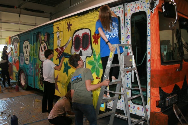 Clarksville Academy students gathered Monday to paint the Spooky Special, a Clarksville Transit System bus that will offer free rides on selected routes on Oct. 30-31.