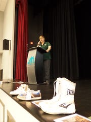 Tricia Baker, co-founder of Attitudes in Reverse, whose son died by suicide, addresses the audience at the annual Youth Services Networking Conference with shoes of teenagers who died by suicide on stage.