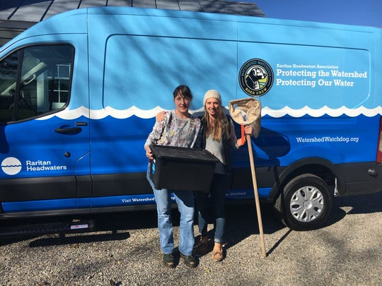 Staff members Mara Tippett, watershed scientist.  left, and Lauren Theis, education director, right, with the new van.