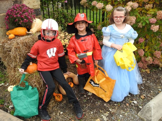 Aidan, Isaiah and Emma Egbert ready to collect candy Tuesday at the Trail of Treats at Clary Gardens.