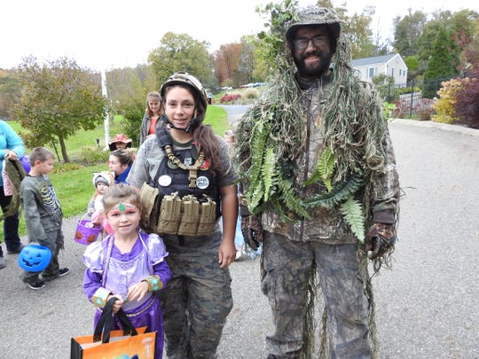 Lyra Gamble and her parents Jusdeanna Hughes and Travis Gamble at the Trail of Treats Tuesday at Clary Gardens.