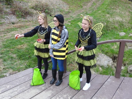 Skylar Quincell, Bella Heddleson and Shelby Minton as bees pass out candy to kids Tuesday for the Trail of Treats at Clary Gardens. Teens gave out nature tips related to the animals they were dressed as to kids as they came by.
