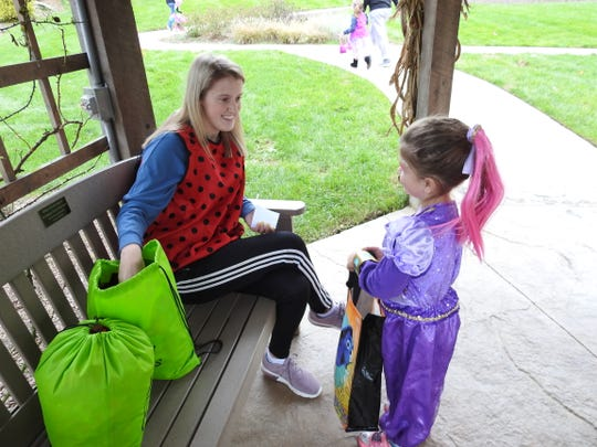 Sydnee Bice of River View High School dressed as a lady bug gives candy to Lyra Gamble, 5, during the Trail of Treats Tuesday at Clary Gardens.