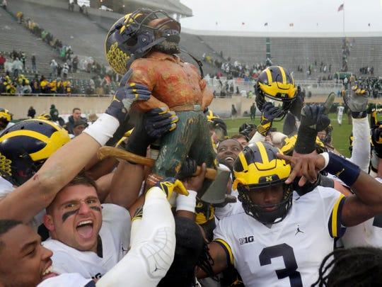 Michigan raises the Paul Bunyan trophy after beating Michigan State, 21-7, on Saturday, October 20, 2018 at Spartan Stadium in East Lansing.
