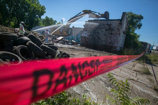 Gayanga Co. laborers Richard Allen of Detroit, left, and Eric Cox of Detroit wet down a demolition on Detroit's west side Monday, July 9, 2018. Detroit's Land Bank demolition program seriously lacks diversity. Just 16 percent of the hundreds of millions in federal dollars awarded since 2014 have gone toward black owned companies. Gayanga Co. has received more than $4 million in contracts and nearly 90 percent of its staff are Detroit residents. We follow them on a commercial demolition on Detroit's west side.