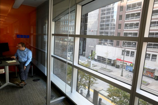 Eric Ostrowski, 25 of Northville, an employee benefits consultant at Plante Moran, takes a business call in one of the rooms looking over Woodward Avenue in downtown Detroit on Tuesday, Oct.23, 2018.