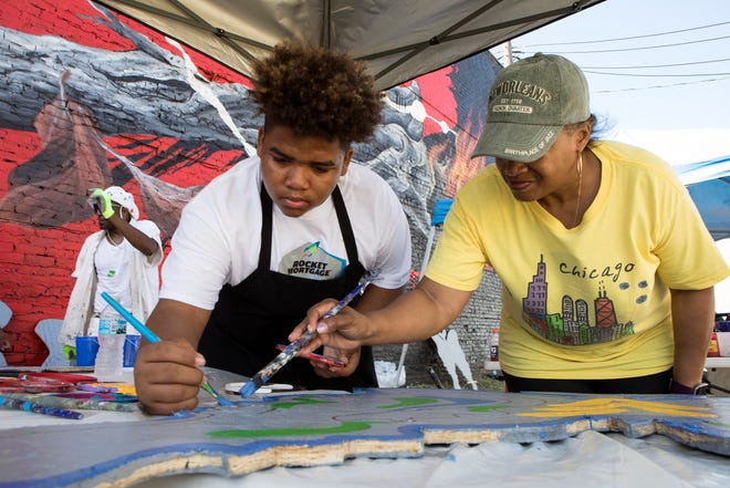 """Da'Vion Nelson, 12 of Detroit and his grandmother Renee Greer, 65 of Southfield paint a butterfly at the interactive mural of artist Charles """"Chazz"""" Miller at Murals in the Market in Detroit, Mich., Sunday, September 16, 2018."""