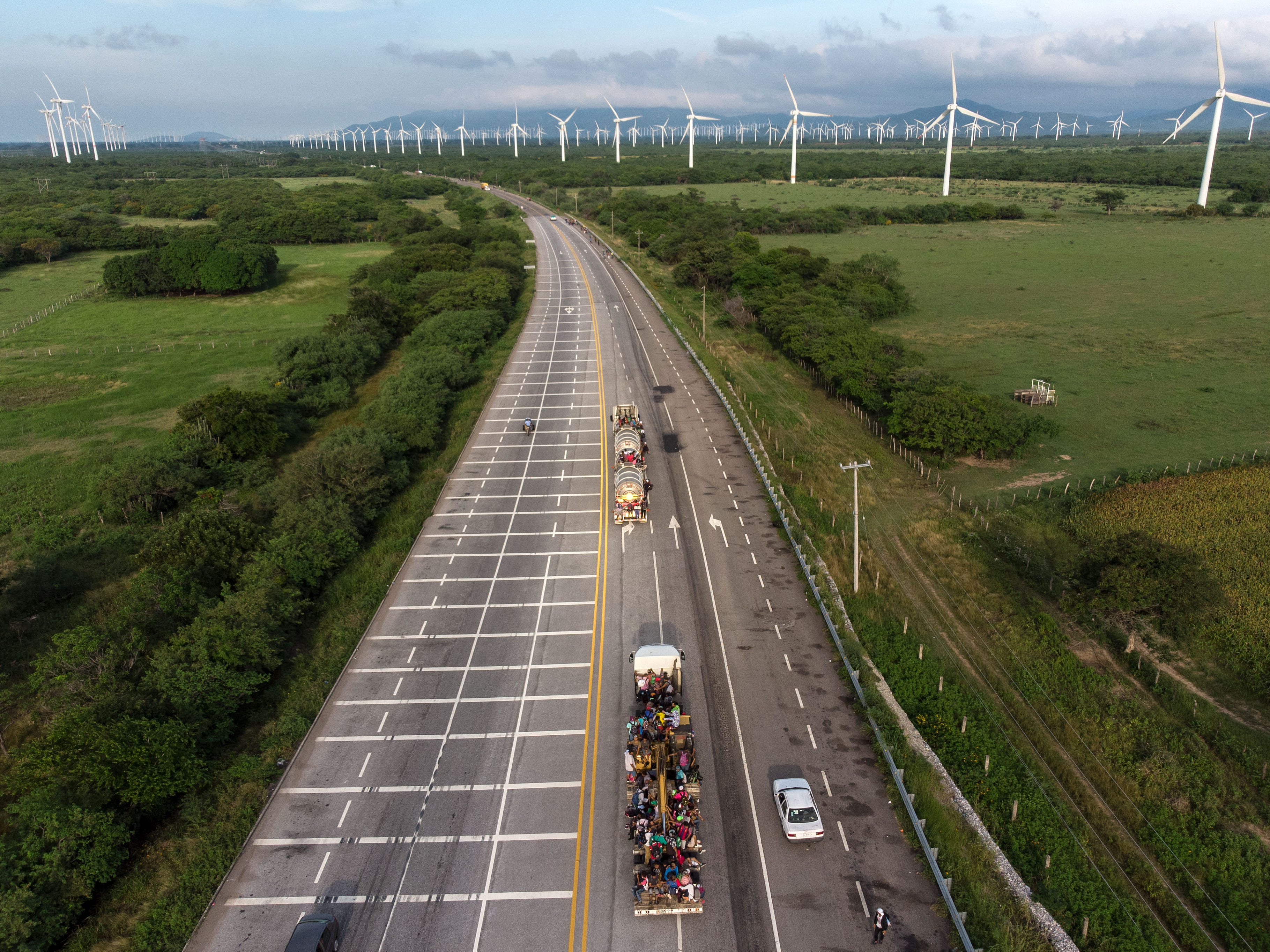 Aerial view shows trucks carrying mostly Honduran migrants taking part in a caravan heading to the U.S. pass near a wind farm on their way from Santiago Niltepec to Juchitan, near the town of La Blanca in Oaxaca State, Mexico, on Oct. 30, 2018. The Pentagon is deploying 5,200 active-duty troops to beef up security along the U.S.-Mexico border, officials announced Monday, in a bid to prevent a caravan of Central American migrants from illegally crossing the frontier.