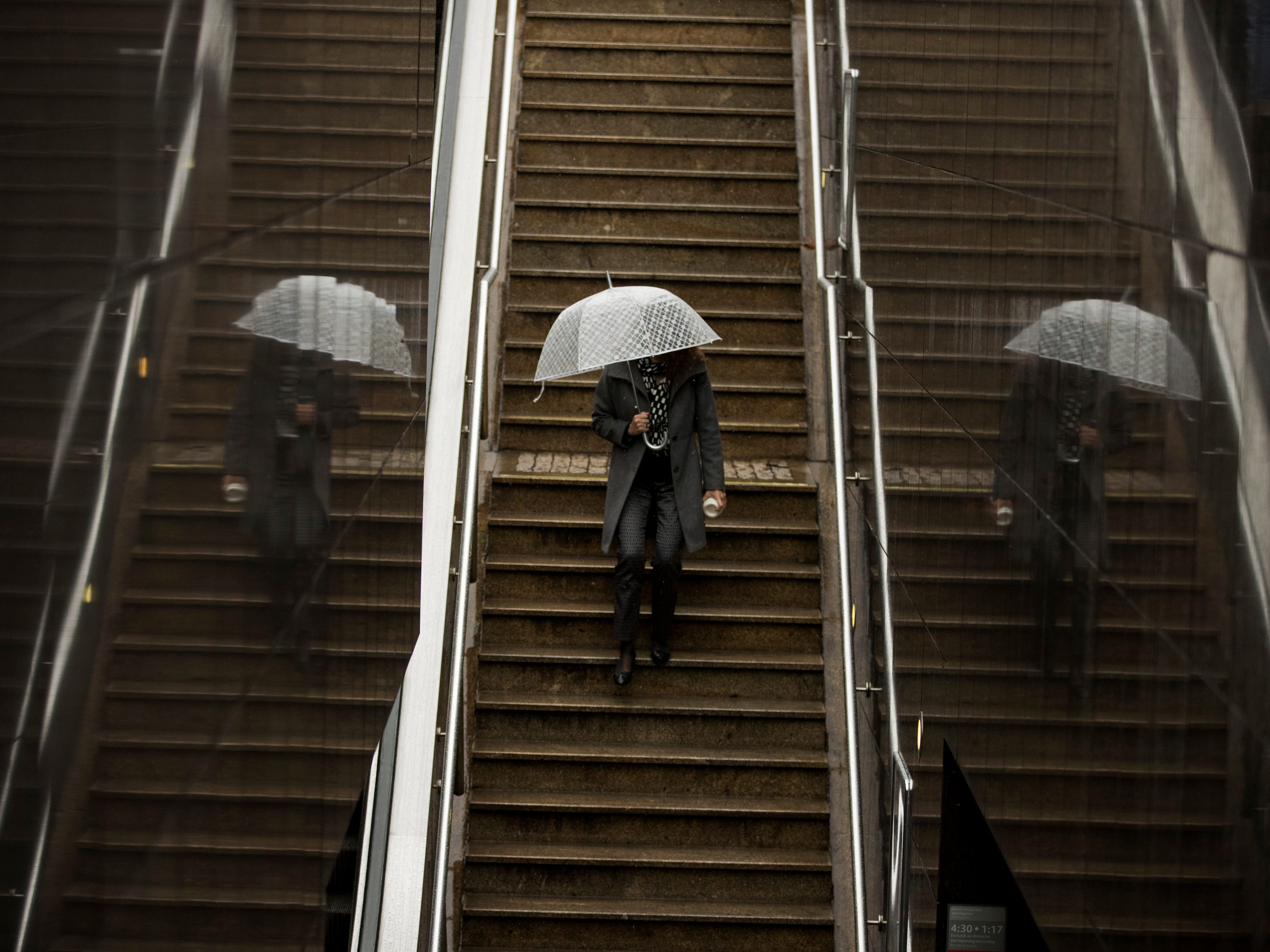 A woman shelters from the rain as she walks down stairs to enter Schuman metro station in Brussels, Tuesday, Oct. 30, 2018.