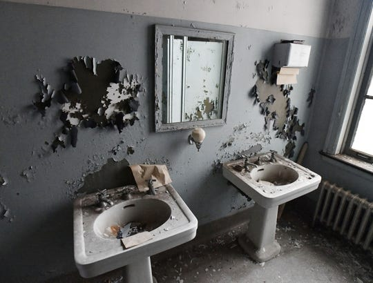 Paint crumbles into old pedestal sinks in a bathroom in the men's ward on the fifth floor.