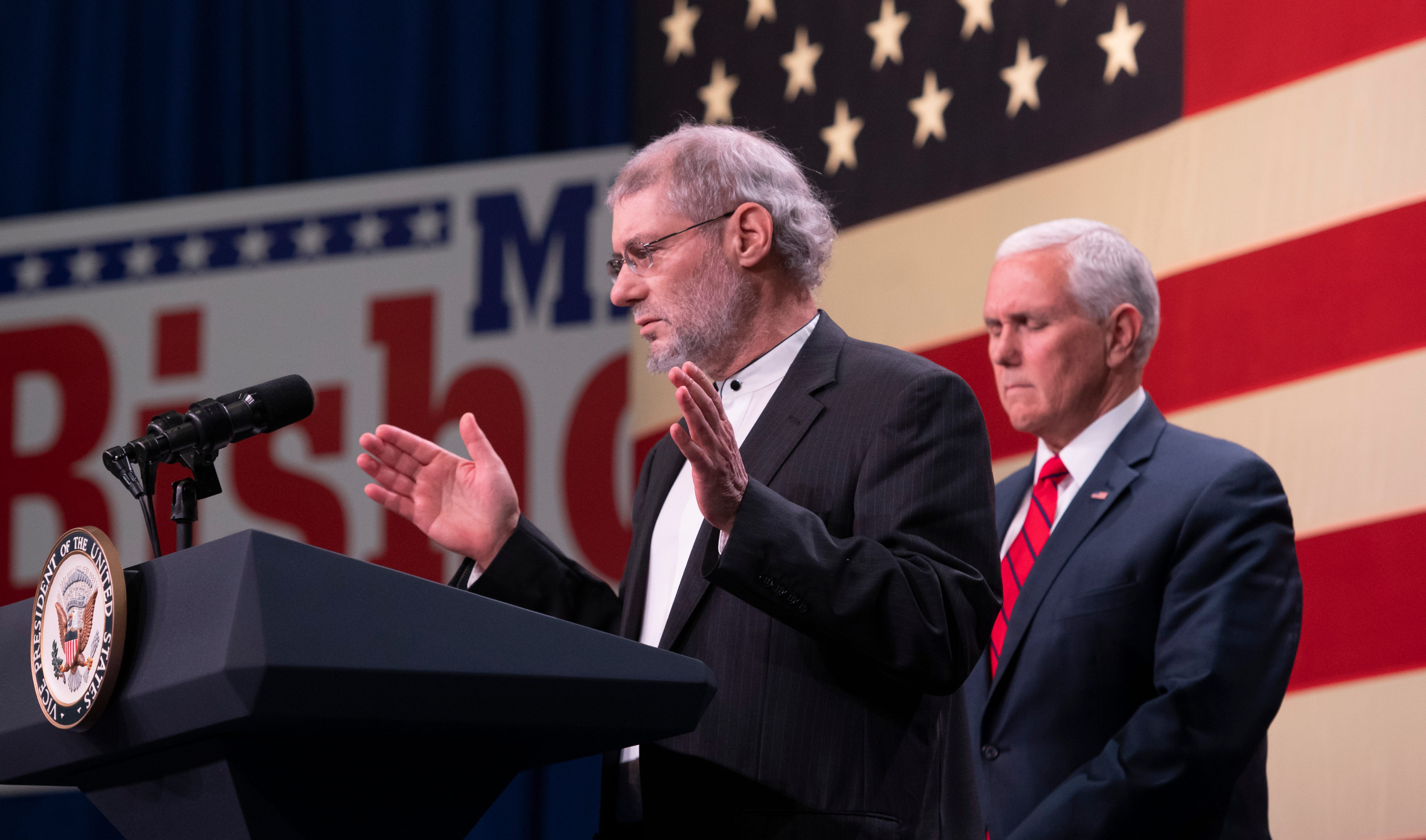 Invited on stage by Vice President Mike Pence, right, Rabbi Loren Jacobs, of congregation Shema Yisrael, says a prayer during a rally featuring GOP political candidates at the Oakland County airport in Waterford, Monday.