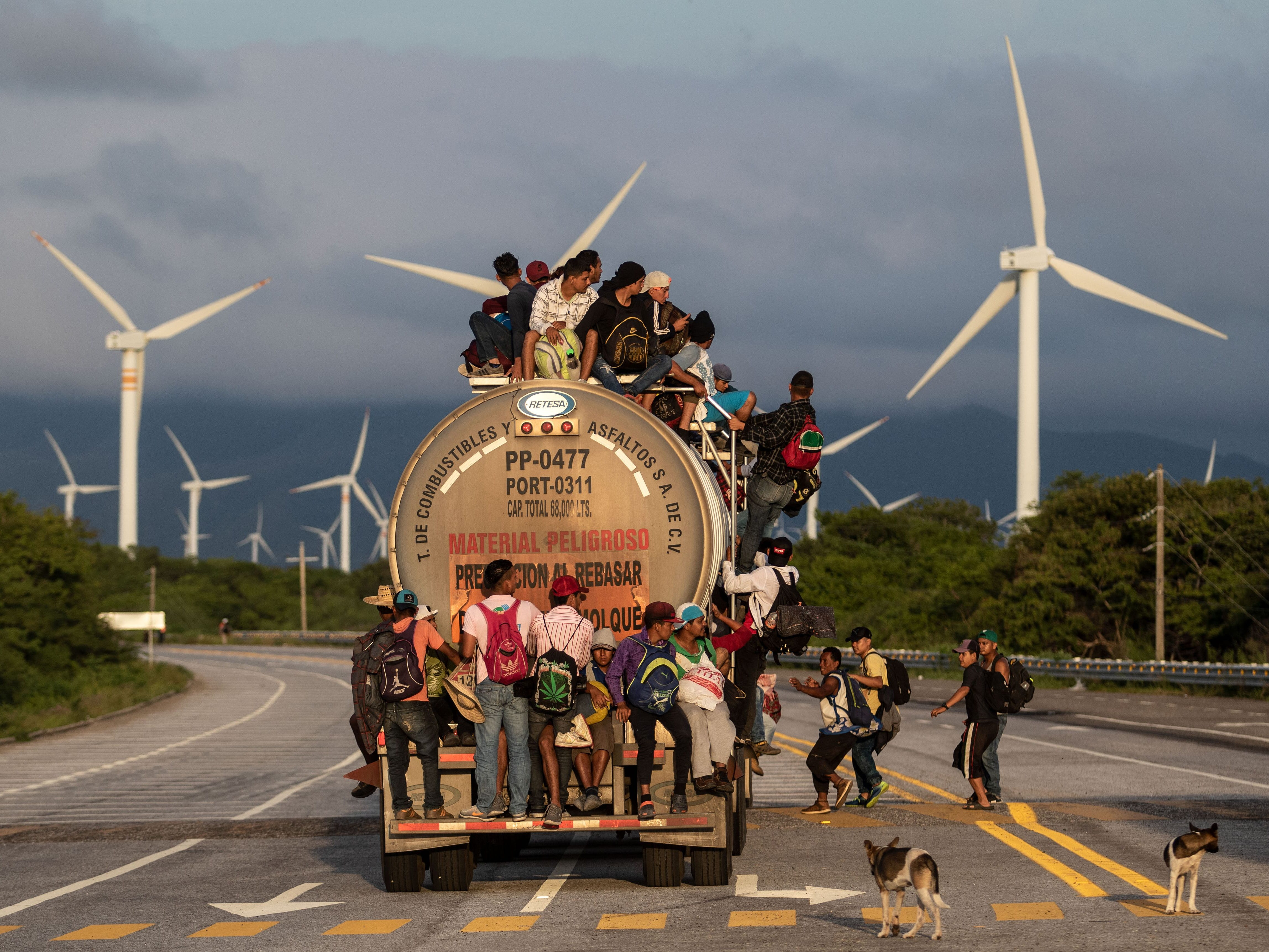 A truck carrying mostly Honduran migrants taking part in a caravan heading to the U.S. passes by a wind farm on their way from Santiago Niltepec to Juchitan, near the town of La Blanca in Oaxaca State, Mexico, on Oct. 30, 2018. The Pentagon is deploying 5,200 active-duty troops to beef up security along the U.S.-Mexico border, officials announced Monday, in a bid to prevent a caravan of Central American migrants from illegally crossing the frontier.