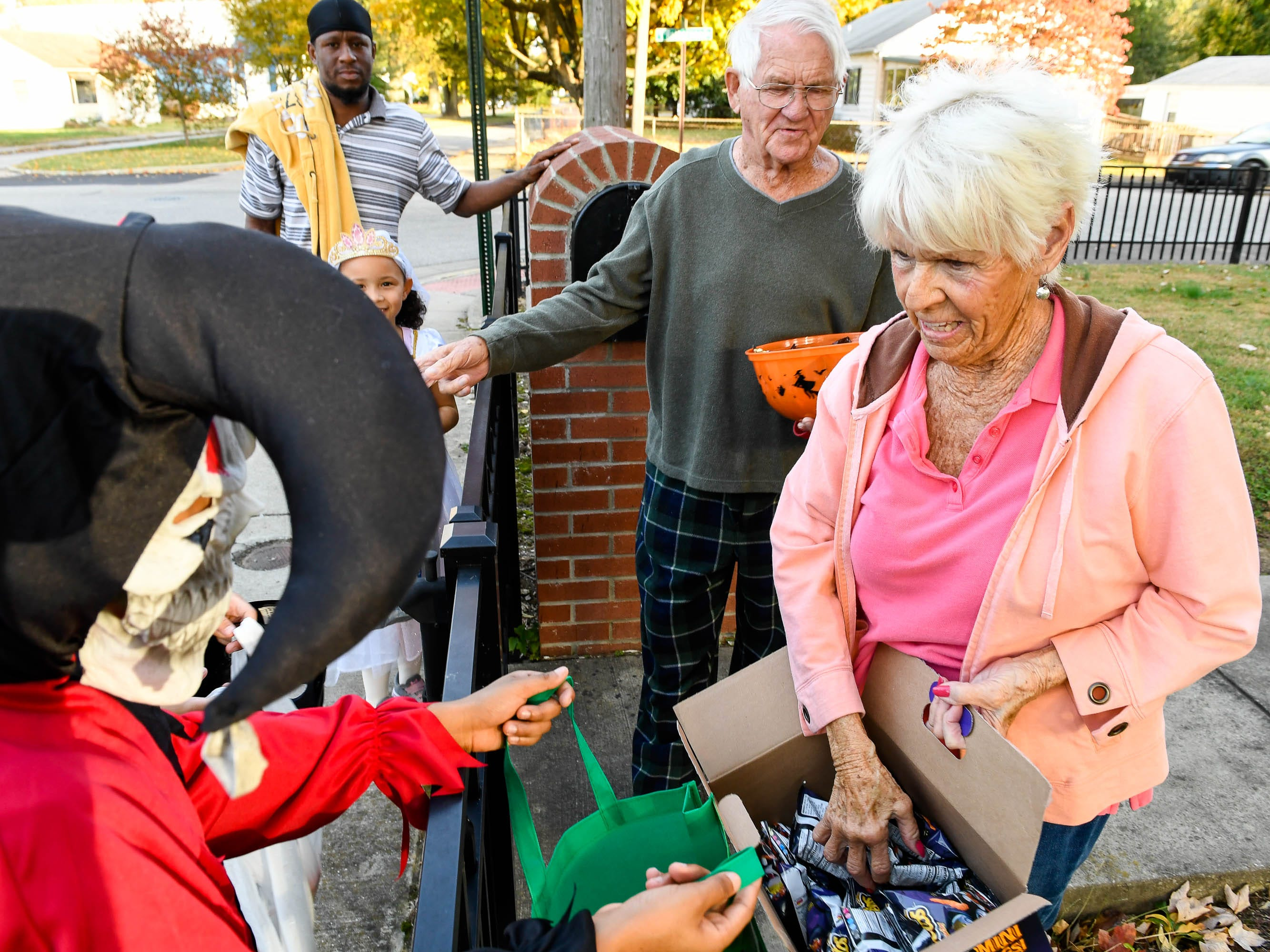 Donna and David Owen hand out candy to trick or treaters on Ravenwood Drive as many revealers went out a day early to avoid possible rain Tuesday, October 30, 2018.