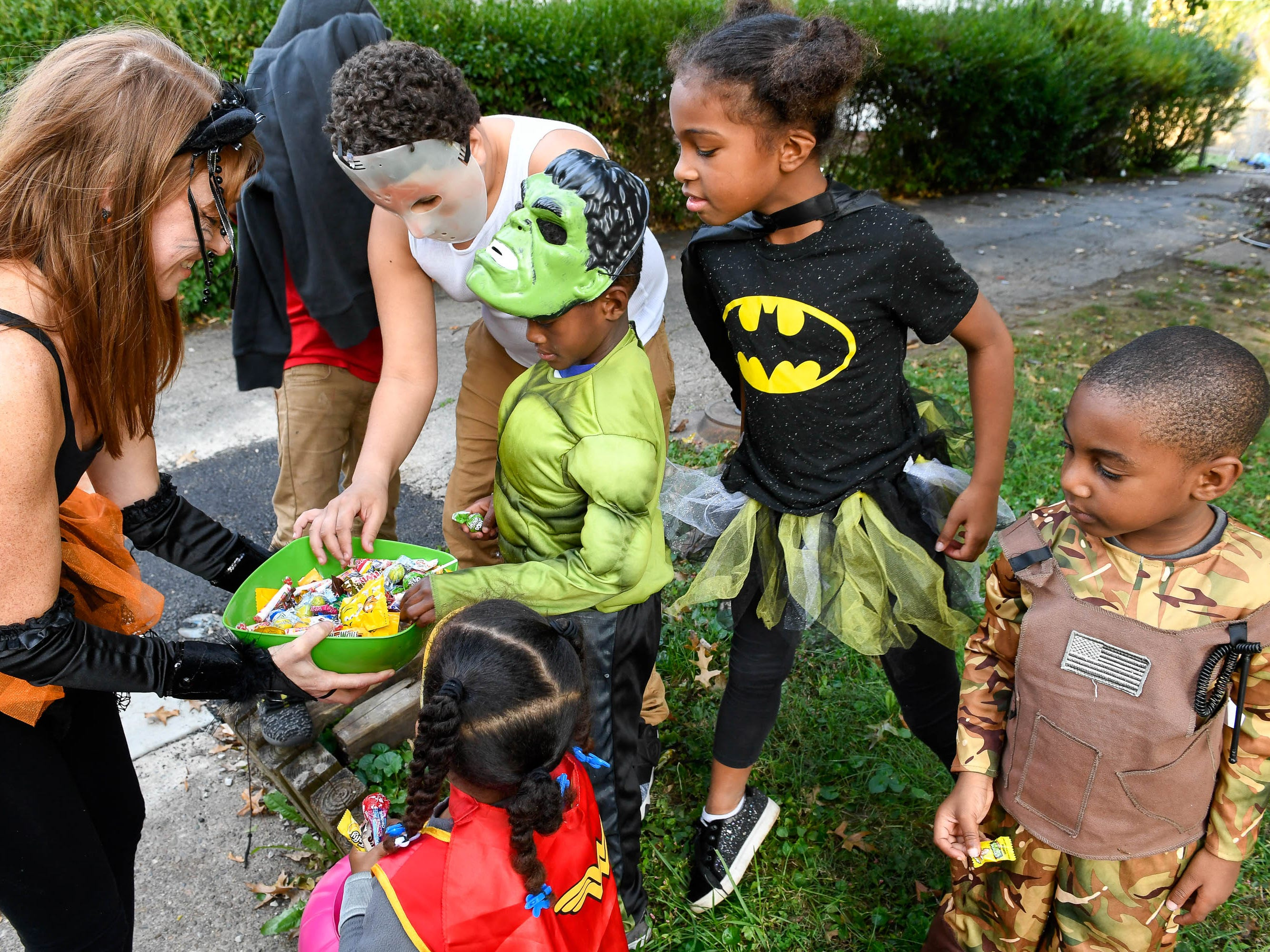 Lindsey Maurer, left, hands out candy to the neighborhood kids on Brookside Drive as many holiday revelers chose to trick or treat early to avoid possible rain in Evansville Tuesday, October 30, 2018.