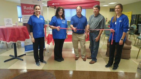 """The Health Hot Spot, a healthy living kiosk and the Salvation Army's newest partnership between Marian University and Anthem Blue Cross Blue Shield, has opened. Pictured at the """"ribbon cutting"""" are Marian University students Autumn (left) and Kara (right) holding the ribbon and Marian University Dr. Chris Laurent, Anthem Blue Cross Blue Shield's David Liethen and Salvation Army Advisory Board representative Steve Zeigler cutting the ribbon, officially """"opening"""" the service to community."""