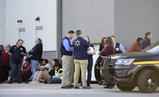 Workers assembled outside of an entrance of Walmart while police turned customers away from the Fremont store on Oct. 22 after a phone threat said a disgruntled person with weapons was going to enter the store.